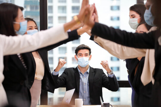 Business people wearing facial mask for new normal and social distancing policy doing high five to the new project after coronavirus in order to survive and avoiding bankruptcy