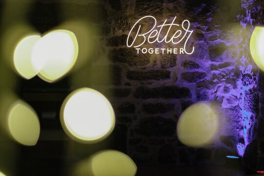 """Neon light text """"Better together"""" on a stone wall with bokeh lights effect"""