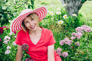 Cottagecore and Staycation at home. Happy elderly blonde woman in hat resting among flowers. Relax in isolation