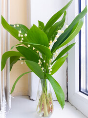 A bouquet of lys in a small glass transparent vase on a wide white plastic window sill.