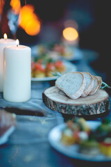 Close up of two lit candles and slices of bread on round wooden board.