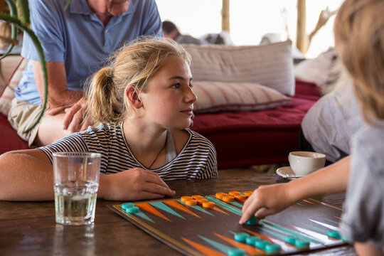 A family on vacation, people playing backgammon at a tented camp in a wildlife reserve.