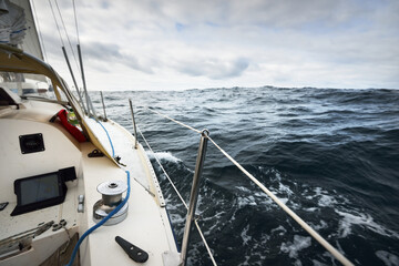 White yacht sailing in the North sea on a cloudy day. Dark storm sky reflecting in the water. Rogaland region, Norway. Sport, recreation, leisure activity theme