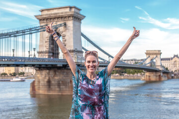 Happy young woman arms raised at Chain Bridge, Budapest