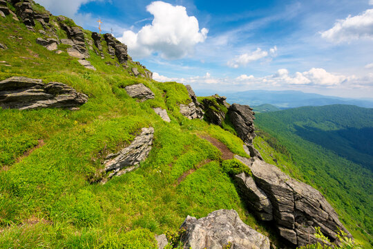 rock on the grassy slope. sunny summer landscape in mountains. ridge in the distance. clouds on the sky. challenging journey