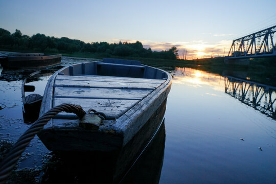 old wooden boats stand on the river in the evening