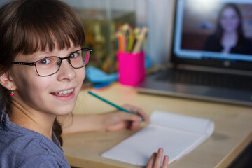 Photo sur Plexiglas Doux monstres Distance learning online education. A happy girl studies at home and does school homework.
