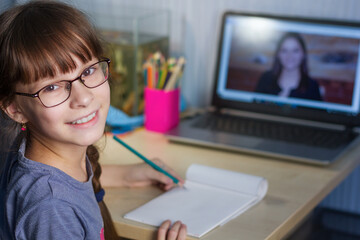 Distance learning online education. A happy girl studies at home and does school homework.