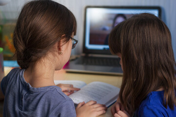 Two girls reading a book. A home distance learning