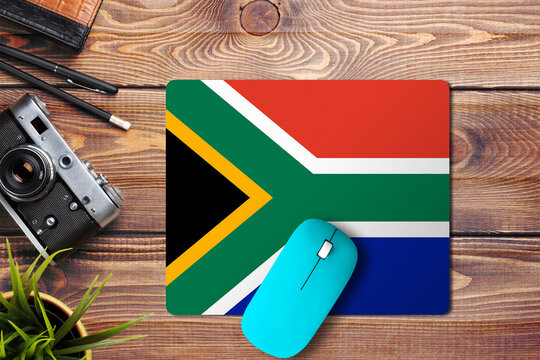 South Africa flag on wooden background with blue wireless mouse on a mouse pad, top view. Digital media concept.