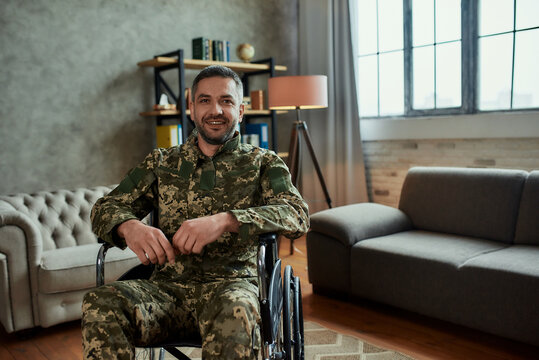 Recovery. Middle aged male military in a wheelchair looking at camera with a smile, during therapy session. Disabled soldier suffering from depression, psychological trauma. PTSD concept