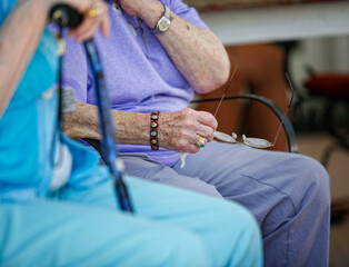 Hands of elderly woman holding glasses