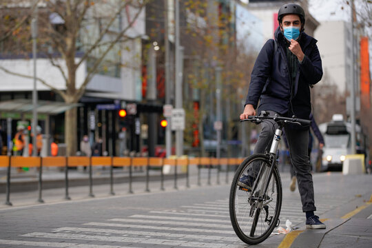 A cyclist adjusts his protective face mask in Melbourne, the first city in Australia to enforce mask-wearing to curb a resurgence of COVID-19