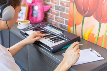 asian male songwriter playing keyboard and writing a song on white music sheet in modern loft living room