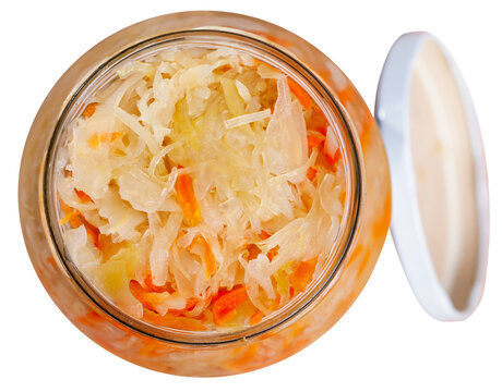 Homemade sauerkraut prepared according to traditional recipe with shredded carrot in glass jar. Isolated over white background