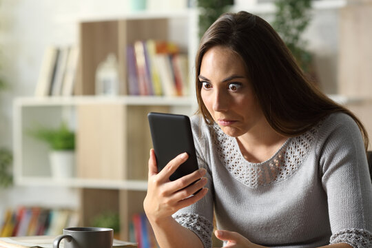 Perplexed woman looking surprised at phone at home