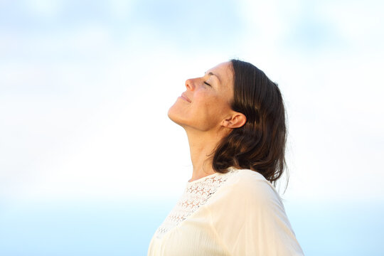 Adult woman breathing fresh air on a beach