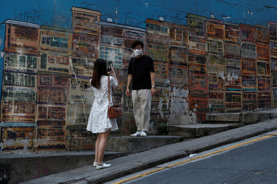 People wearing surgical masks take a photo at Central following the coronavirus disease (COVID-19) outbreak in Hong Kong