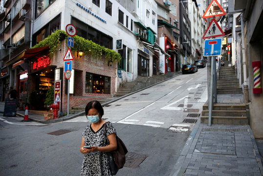 A woman wears a surgical mask while walking at Central following the coronavirus disease (COVID-19) outbreak in Hong Kong,