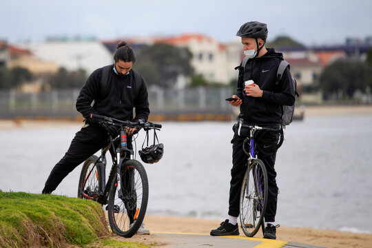 Bicyclists wear face masks at St Kilda beach in Melbourne, the first city in Australia to enforce mask-wearing to curb a resurgence of COVID-19