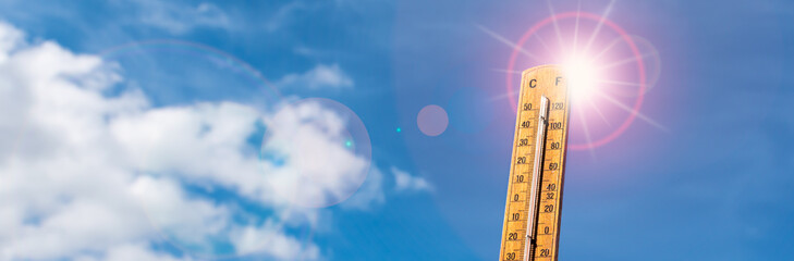 Thermometer against blue sunny sky. Hot summer weather concept.