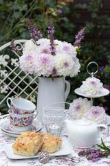 Tischdekoration mit Butterkuchen, Porzellan und Dahlienstrauß in Weiß und Lila
