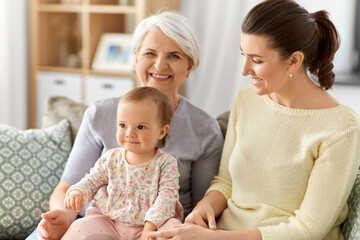 family, generation and female concept - happy smiling mother, baby daughter and grandmother sitting on sofa at home