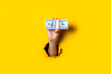 Female hand holds horizontally a bundle of money bills on a yellow background.