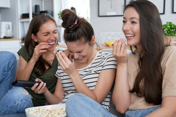 Three friends laughing while watching TV