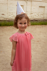 Adorable little girl in pink dress and party hat looking at camera with smile while standing on sandy playground during birthday celebration in summer day