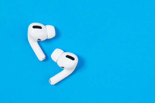 Rostov, Russia - July 06, 2020: Apple AirPods Pro on a blue background. Silent wireless headphones close up.