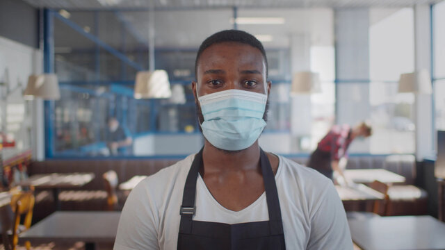 Portrait of afro-american waiter wearing protective mask looking at camera