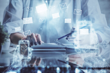 E-mail abstract envelop drawing over hands taking notes background. Concept of electronic mail. Double exposure