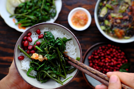 people have lunch, hand hold rice bowl with Vietnamese vegan food background