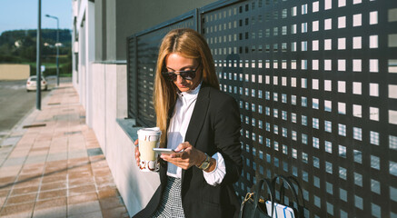 Businesswoman using mobile and drinking coffee sitting on a wall