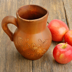 Apple cider in a ceramic jug on wooden table.