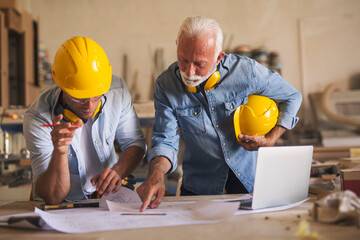 Woodworkers watching at the blueprints
