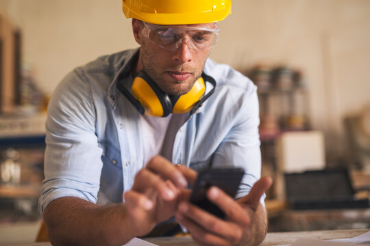Close up of young carpenter using mobile phone