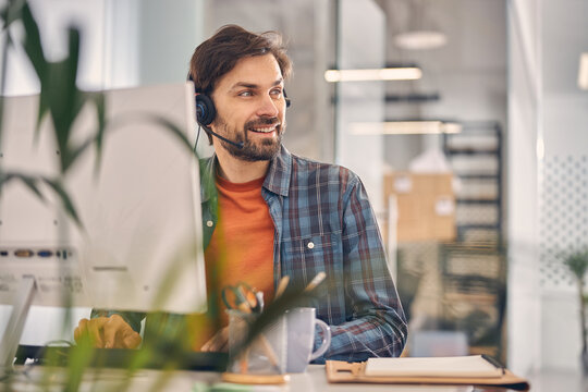 Joyful male worker sitting at the table in office