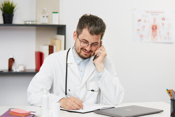 doctor talking on phone and noting down the data