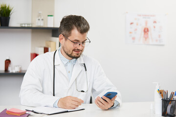 senior physician in white gown using smartphone at work