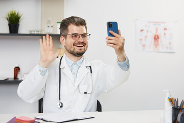 doctor having video call with patients at his medical cabinet