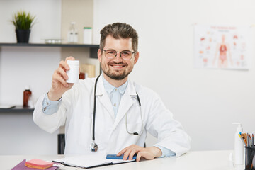 doctor holding jar of tablets and smiling to camera