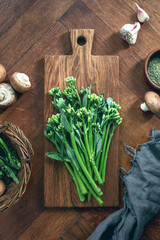 Broccolini fresh bunch on a rustic cutting board ready for cooking