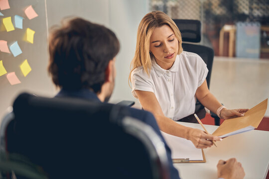Beautiful young woman having meeting with client in office