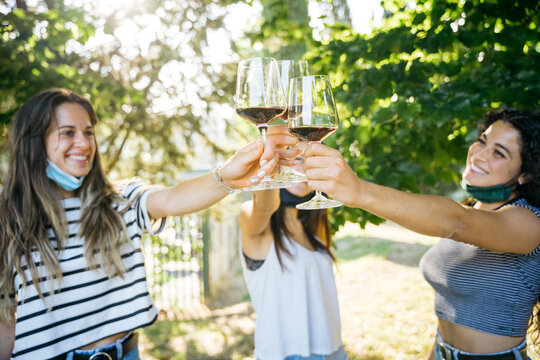 Young millennial women toasting in a park with red wine glasses in a tasting of a restaurant - Group of people having fun together - Friends in a relax moment