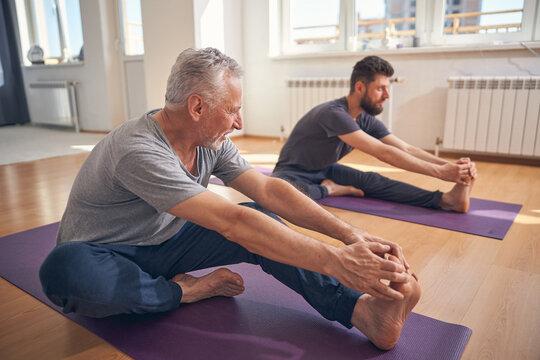 Beginner yogi and his coach practicing yoga