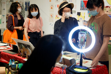People wear masks as they at printed art works at the abC Art Book Fair following an outbreak of the coronavirus disease (COVID-19) in Beijing