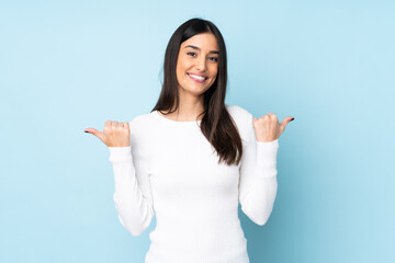 Young caucasian woman isolated on blue background with thumbs up gesture and smiling