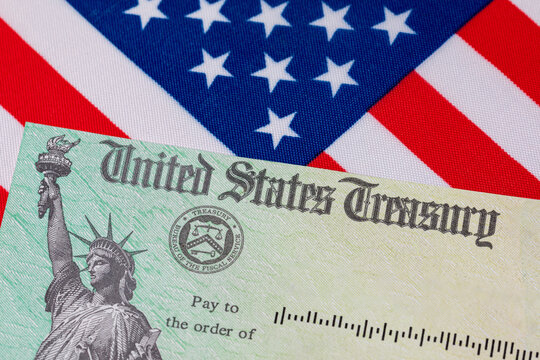 United States Treasury check and American flag. Concept of stimulus payment, tax refund. Federal government grants, loans, benefits and assistance